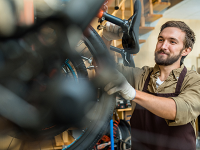 Professional repairman with spanner fixing detail of bicycle wheel